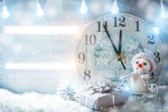 圣诞节冬天背景,小雪人站立与时钟 新年好 快活的圣诞节 免版税库存照片