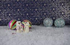 圣诞节冬天蛋白软糖的照片图象塑造了,与特征模式的雪人在与中看不中用的物品装饰的背景中 免版税图库摄影