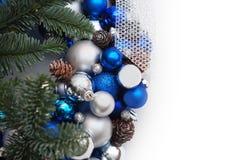圣诞节冬天装饰花圈背景 蓝色和银色地球或球与冷杉分支,在白色 图库摄影