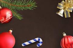 圣诞节冷杉分支、棍子、红色波浪和愚钝的球和响铃在黑暗的背景 免版税库存图片