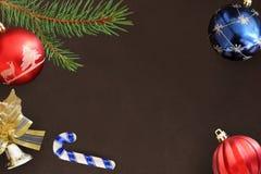 圣诞节冷杉分支、棍子、红色波浪和蓝色球和装饰响铃在黑暗 库存照片