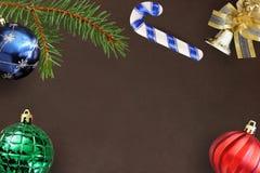 圣诞节冷杉分支、棍子、蓝色、绿色和红色波浪气球和装饰响铃在黑暗的背景 免版税库存照片