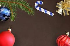 圣诞节冷杉分支、棍子、蓝色和红色波浪气球和装饰响铃在黑暗的背景 免版税图库摄影