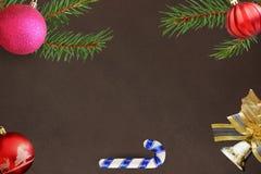 圣诞节冷杉分支、棍子,红色波浪和桃红色球,在黑暗的背景的响铃装饰 免版税库存照片