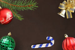 圣诞节冷杉分支、棍子,红色波浪和绿色有肋骨球,在黑暗的响铃 库存照片
