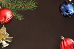 圣诞节冷杉分支、红色波浪和蓝色球和装饰响铃在黑暗 库存图片