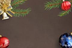 圣诞节冷杉分支、红色波浪和蓝色球和装饰响铃在黑暗 免版税库存图片