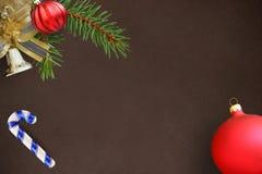 圣诞节冷杉分支、红色波浪愚钝的球、棍子和响铃在黑暗的背景 免版税库存照片