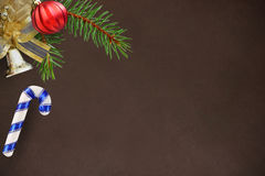 圣诞节冷杉分支、红色波浪球、棍子和响铃在黑暗的背景 免版税图库摄影