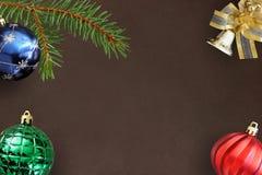 圣诞节冷杉分支、蓝色、绿色有肋骨和红色波浪气球和装饰响铃在黑暗 免版税图库摄影