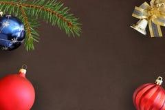 圣诞节冷杉分支、蓝色和红色波浪愚钝的气球和装饰响铃在黑暗 免版税库存照片