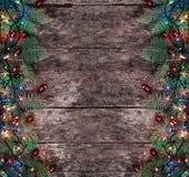 圣诞节冷杉分支与光和红色装饰在木背景 Xmas和新年快乐构成 图库摄影