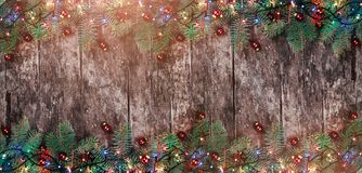 圣诞节冷杉分支与光和红色装饰在木背景 Xmas和新年快乐框架 免版税库存照片
