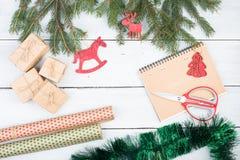 圣诞节冷杉分支,圣诞节玩具,礼物盒,剪刀,笔记薄,包装纸 免版税库存图片