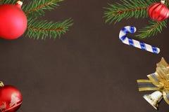 圣诞节冷杉分支,棍子,红色波浪愚钝的球,在黑暗的背景的响铃装饰 免版税库存照片