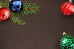 圣诞节冷杉分支,波浪红色,蓝色和绿色有肋骨球在黑暗 免版税图库摄影