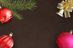 圣诞节冷杉分支,红色波浪和桃红色球,在黑暗的bac的响铃 库存照片