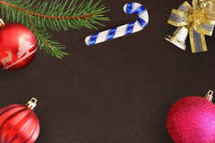 圣诞节冷杉分支,红色波浪和桃红色球,棍子,在黑暗的响铃 免版税库存图片