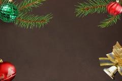 圣诞节冷杉分支,红色波浪和绿色有肋骨球,在黑暗的响铃装饰 免版税库存图片