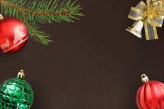 圣诞节冷杉分支,红色波浪和绿色有肋骨球,在黑暗的响铃 库存照片