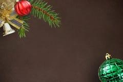 圣诞节冷杉分支,红色波浪和绿色有肋骨球,在黑暗的响铃 库存图片