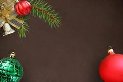 圣诞节冷杉分支,红色波浪愚钝和绿色有肋骨球,在黑暗的响铃 库存图片