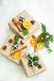 圣诞节减速火箭的被包裹的礼物用香料,干橙色切片和 免版税库存照片