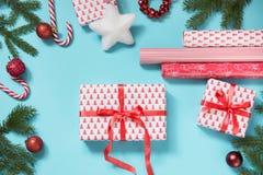 圣诞节创造性的礼物盒包裹与红色丝带和在蓝色组成的工作区 平的位置 顶视图 免版税库存照片