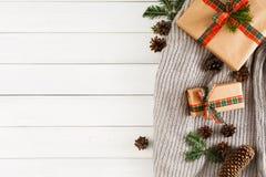 圣诞节创造性的箱子,在白色木背景的被编织的围巾 免版税库存图片