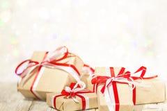 圣诞节反对bokeh背景的礼物盒 假日用雪装饰的贺卡 库存照片