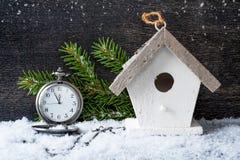 圣诞节古色古香的时钟和一个鸟舍在木背景 库存照片
