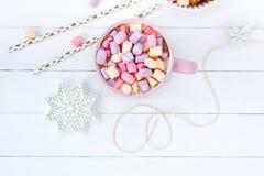 圣诞节可可粉蛋白软糖桃红色杯子和姜饼干白色木桌山莓果酱 库存照片