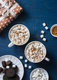 圣诞节启发桌-热巧克力用蛋白软糖,曲奇饼,礼物盒,圣诞节在蓝色背景的装饰品驯鹿 库存图片