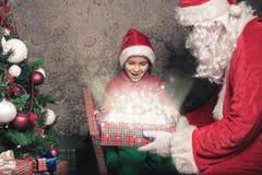 圣诞节启发!愉快的震惊男孩惊奇看圣诞老人 库存图片