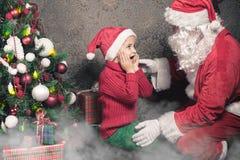圣诞节启发!愉快的震惊男孩惊奇看圣诞老人 免版税库存照片