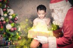 圣诞节启发!愉快的震惊男孩惊奇看圣诞老人 库存照片