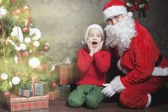 圣诞节启发!愉快的震惊男孩惊奇看圣诞老人 免版税库存图片