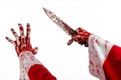 圣诞节和万圣夜题材:拿着在被隔绝的白色背景的狂人的圣诞老人的血淋淋的手一把血淋淋的刀子 免版税库存图片