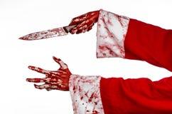 圣诞节和万圣夜题材:拿着在被隔绝的白色背景的狂人的圣诞老人的血淋淋的手一把血淋淋的刀子 免版税库存照片