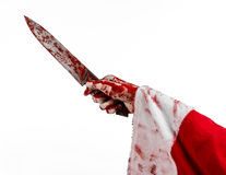 圣诞节和万圣夜题材:拿着在被隔绝的白色背景的狂人的圣诞老人的血淋淋的手一把血淋淋的刀子 免版税图库摄影