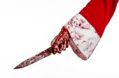 圣诞节和万圣夜题材:拿着在被隔绝的白色背景的狂人的圣诞老人的血淋淋的手一把血淋淋的刀子 库存照片