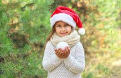 圣诞节和人概念-圣诞老人帽子的小微笑的女孩孩子有雪球的 免版税图库摄影