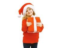 圣诞节和人概念-圣诞老人帽子的微笑的小女孩 库存图片