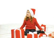 圣诞节和人概念-圣诞老人帽子的快乐的小女孩 免版税图库摄影