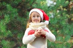 圣诞节和人概念-圣诞老人红色帽子的小女孩孩子有球的 图库摄影