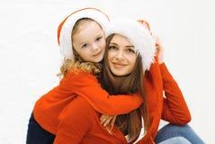 圣诞节和人概念-母亲和孩子圣诞老人帽子的 库存图片