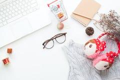 圣诞节和冬天购物的网上概念顶视图在白色书桌上的 白色膝上型计算机,购物车,礼物盒,笔记本, eyeglas 库存照片