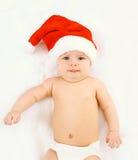 圣诞节和家庭观念-说谎在白色床家的红色圣诞老人帽子的逗人喜爱的婴孩 库存照片