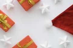 圣诞节和新年与礼物盒的假日构成,圣诞老人帽子,丝带,在白色背景的星 顶视图 图库摄影