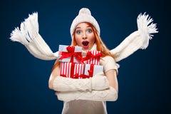 圣诞节和新年假日 拿着在冬天背景的惊奇的妇女礼物盒与在黑星期五的雪 销售额 免版税库存照片